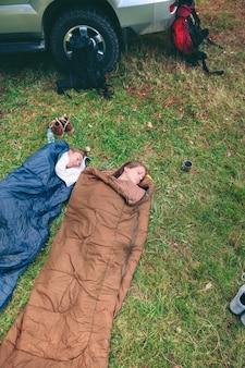 Bovenaanzicht van jonge, mooie vrouwenvrienden die in de natuur slapen in slaapzakken met hun rugzakken en 4x4-voertuig