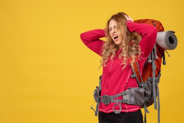 Bovenaanzicht van jonge onrustige reizende meisje dat haar bagage verzamelt en aan hoofdpijn lijdt
