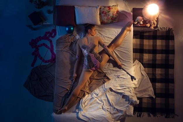 Bovenaanzicht van jonge professionele ritmische turnster die in sportkleding in haar slaapkamer slaapt