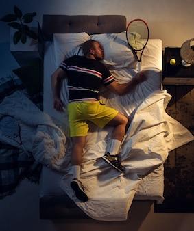 Bovenaanzicht van jonge professionele tennisser slapen in zijn slaapkamer in sportkleding met racket