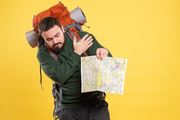 Bovenaanzicht van jonge reizende man met rugzak die een kaart vasthoudt en last heeft van schouderpijn op geel