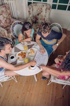 Bovenaanzicht van jonge toeristische vrienden die kaarten kijken en 's ochtends genieten van een gezond ontbijt. vakantie en toerisme concept.