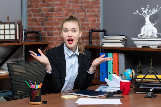 Bovenaanzicht van jonge verbaasde en emotionele vrouwelijke assistent die aan haar bureau op kantoor zit