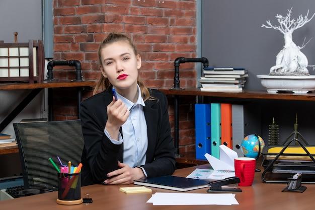Bovenaanzicht van jonge verwarde vrouwelijke assistent zittend aan haar bureau op kantoor