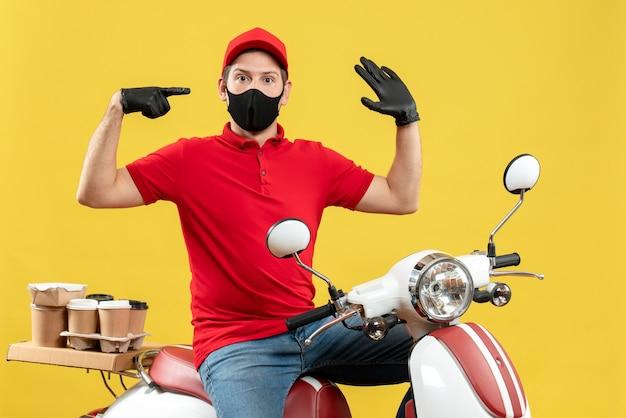 Bovenaanzicht van jonge volwassene die rode blouse en muts handschoenen in medisch masker draagt ?? die bestelling levert, zittend op een scooter, gevoel verward op gele achtergrond