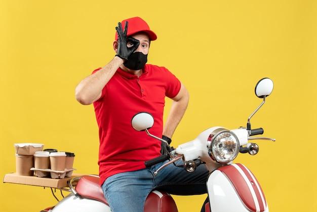 Bovenaanzicht van jonge volwassene dragen rode blouse en hoed handschoenen in medisch masker leveren bestelling zittend op scooter bril gebaar maken