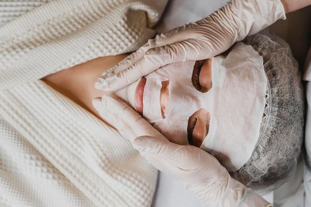 Bovenaanzicht van jonge vrouw die een behandeling van het huidmasker krijgt