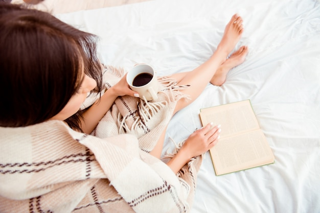 Bovenaanzicht van jonge vrouw leesboek en zonnebaden met plaid en koffie