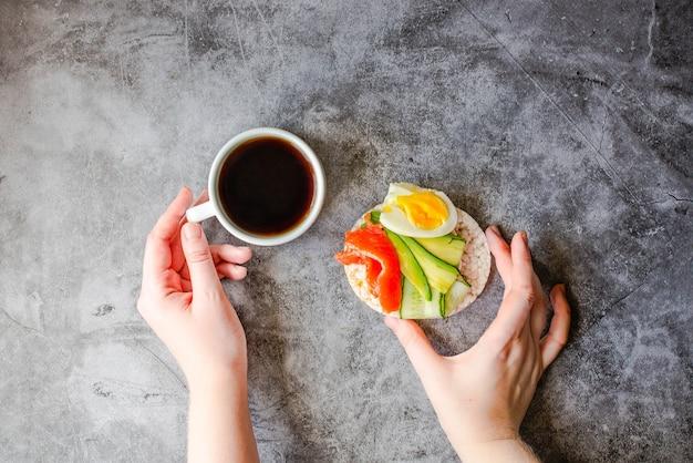 Bovenaanzicht van jonge vrouw met een lunchpauze. rijstkrokante cakejes met avocado en vers gezouten zalm. mannelijke handen met voedsel dat rijk is aan vet en eiwit en kopje koffie. ruimte voor tekst.