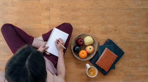 Bovenaanzicht van jonge vrouw schrijven op notitieblok met potlood zittend op de vloer thuis.