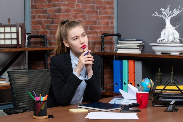 Bovenaanzicht van jonge vrouwelijke assistent zittend aan haar bureau in diepe gedachten op kantoor