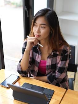 Bovenaanzicht van jonge vrouwelijke student na te denken over haar opdracht tijdens het gebruik van digitale tablet in bibliotheek