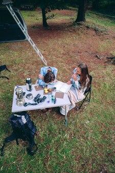 Bovenaanzicht van jonge vrouwen die ontbijten op een camping boven een natuur