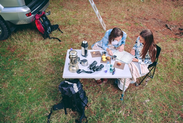 Bovenaanzicht van jonge vrouwen op zoek naar wegenkaart op een camping