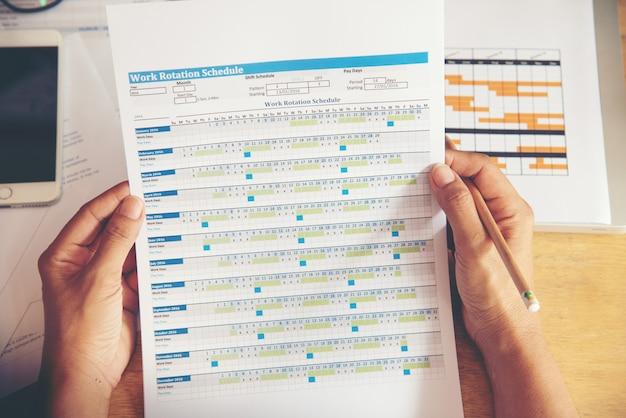 Bovenaanzicht van jonge werkende vrouw met behulp van laptop en het lezen van rapport, grafieken, grafieken, document op het werk. bedrijfs vrouw die bij haar bureau werkt.