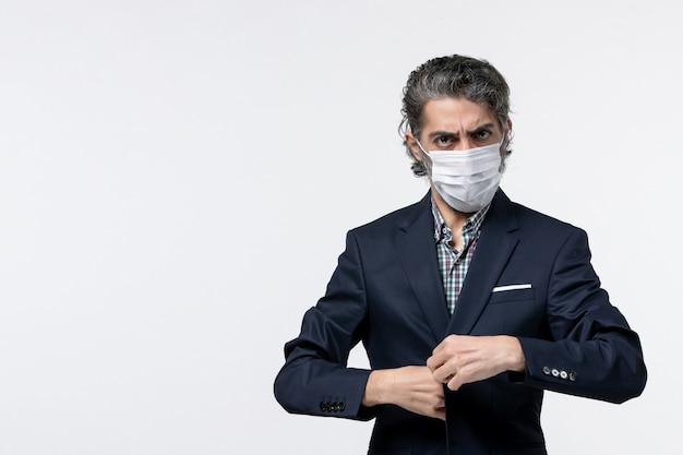 Bovenaanzicht van jonge zakenman in pak met masker en poseren voor camera op witte ondergrond camera