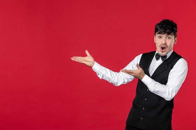 Bovenaanzicht van jonge zich afvragende mannelijke ober in een uniform met vlinderdas en met beide handen aan de rechterkant omhoog wijzend