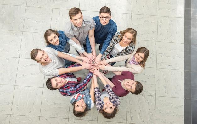 Bovenaanzicht van jongeren met hun handen samen.