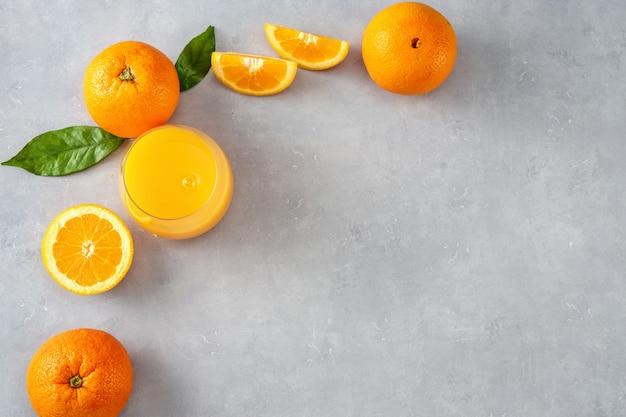 Bovenaanzicht van jus d'orange glas, sinaasappels en plakjes
