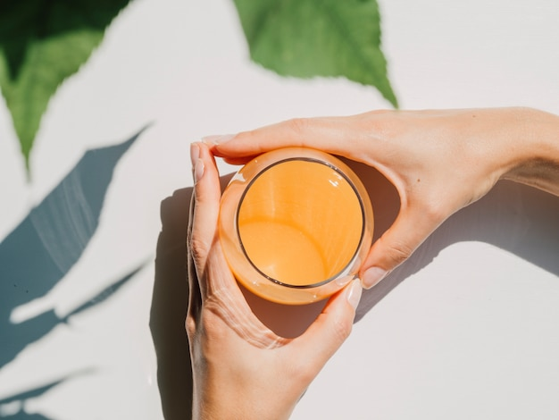 Bovenaanzicht van jus d'orange met handen van de vrouw