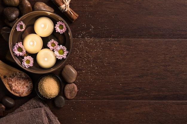 Bovenaanzicht van kaarsen met zout en kiezelstenen op houten achtergrond met kopie ruimte.