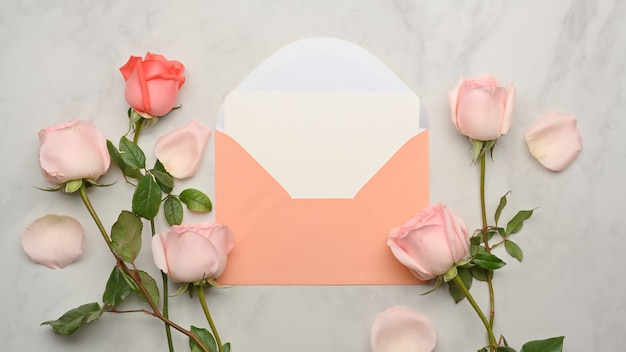 Bovenaanzicht van kaart, pastel envelop en roze rozen bloeien op marmeren bureau