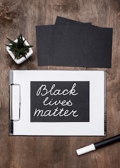 Bovenaanzicht van kaarten met zwarte levensmoeilijkheden met klembord en plant