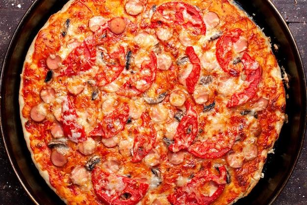 Bovenaanzicht van kaasachtige tomatenpizza met olijven en worstjes in de pan op bruin bureau
