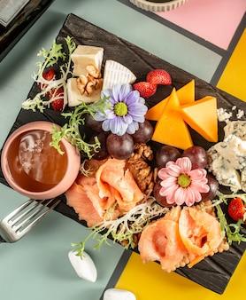 Bovenaanzicht van kaasplaat met gerookte zalm, blauwe kaas, cheddar, druif en bloemen
