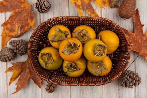 Bovenaanzicht van kaki fruit op een emmer met bladeren geïsoleerd op een grijze houten tafel
