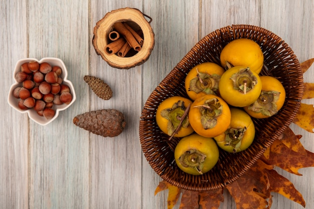 Bovenaanzicht van kaki fruit op een emmer met hazelnoten op een kom met kaneelstokjes op een houten pot op een grijze houten tafel