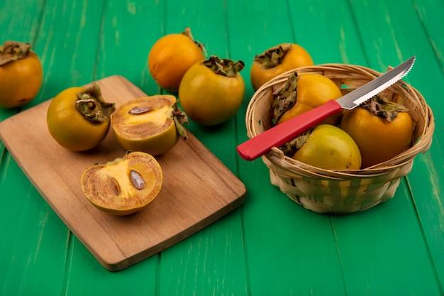 Bovenaanzicht van kaki fruit op een emmer met mes met gehalveerde kaki fruit op een houten keukenplank op een groene houten tafel
