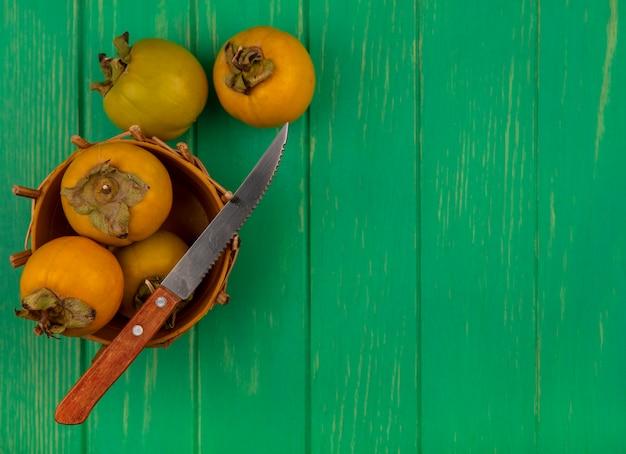 Bovenaanzicht van kaki fruit op een emmer met mes op een groene houten tafel met kopie ruimte