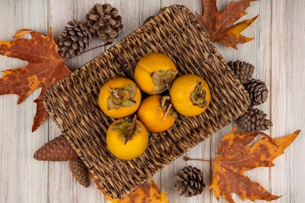 Bovenaanzicht van kaki fruit op een rieten dienblad met bladeren op een grijze houten tafel