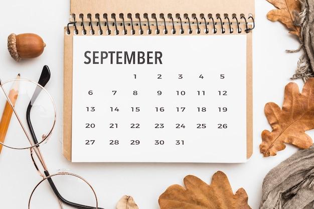 Bovenaanzicht van kalender met herfstbladeren en glazen