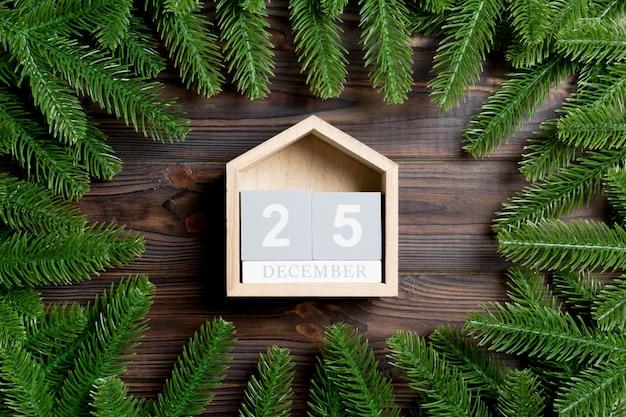 Bovenaanzicht van kalender versierd met een frame gemaakt van dennenboom op houten tafel. vijfentwintig december. kerst tijd concept
