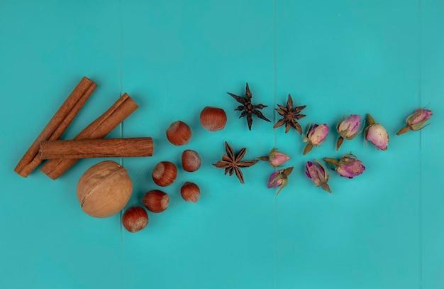 Bovenaanzicht van kaneel met noten walnoot en bloemen op blauwe achtergrond