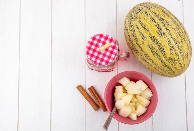 Bovenaanzicht van kantaloepmeloen met kaneelstokjes met sap in een glazen pot op wit hout