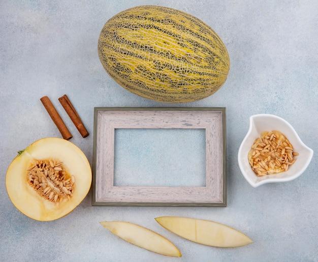 Bovenaanzicht van kantaloepmeloen met pijpjes kaneel met zaden van meloen op witte kom op wit