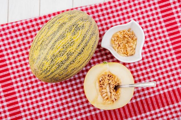 Bovenaanzicht van kantaloepmeloen met zaden op witte kom op rood geruit tafelkleed op wit