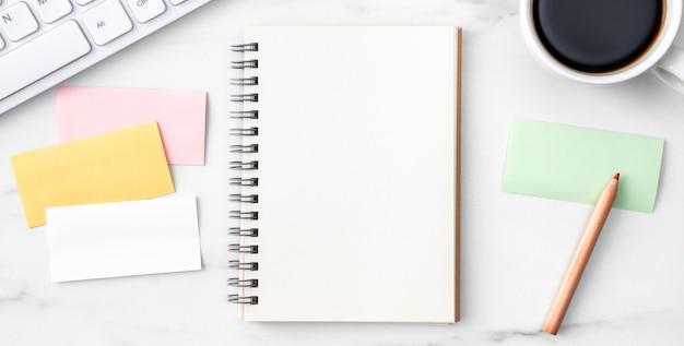 Bovenaanzicht van kantoor tafel bureau gezellig werk concept met toetsenbord, notebook, potlood, brillen en koffie op heldere marmeren witte achtergrond.