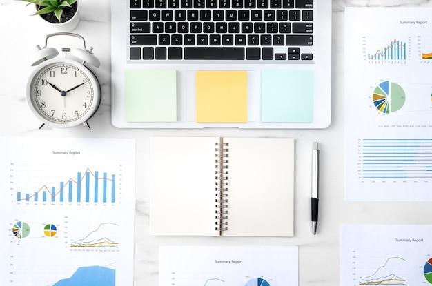 Bovenaanzicht van kantoor tafel bureau werk concept met lege notebook, rapport, wekker op marmeren witte achtergrond, concept van timingbeheer en planningsplanning.