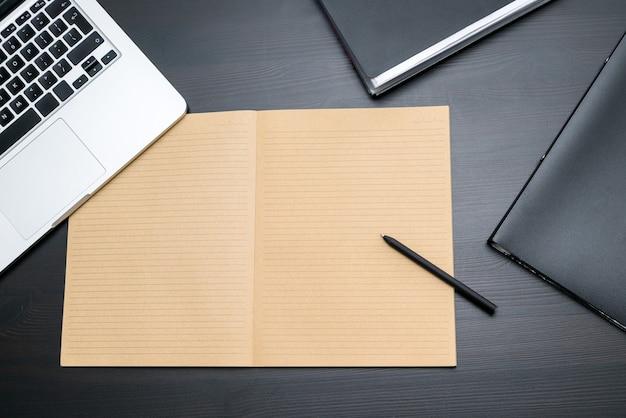 Bovenaanzicht van kantoor tafel met lege notebook en pen.