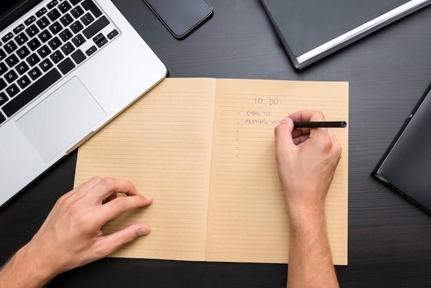 Bovenaanzicht van kantoor tafel met mans handen schrijven takenlijst met pen op vintage notebook