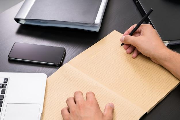 Bovenaanzicht van kantoor tafel met mans handen schrijven takenlijst