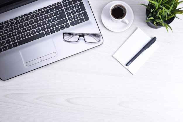 Bovenaanzicht van kantoor werkruimte, houten bureau tafel met laptop notebook, toetsenbord, pen, bril, telefoon, notebook en kopje koffie. met kopieerruimte, plat leggen. mock up.