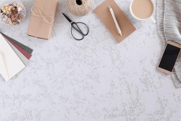 Bovenaanzicht van kantoorbenodigdheden en accessoires, mobiele telefoon, geschenkdozen, envelop en kopje latte koffie. minimalistische platte lay-out, vintage stijl thuiskantoor bureau werkruimte