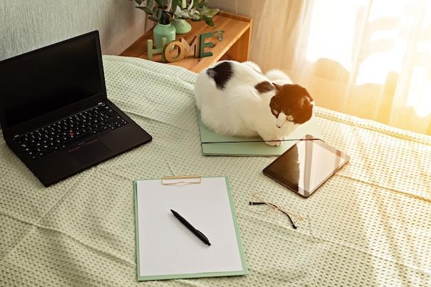 Bovenaanzicht van kantoorbenodigdheden in het bed, informele werkomgeving met laptop, kladblok, theekopje. werk op afstand, thuiskantoor, freelancer, zelfisolatieconcept