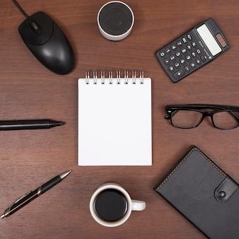Bovenaanzicht van kantoorbenodigdheden; koffiekop; met bluetooth speaker; lenzenvloeistof op houten bureau