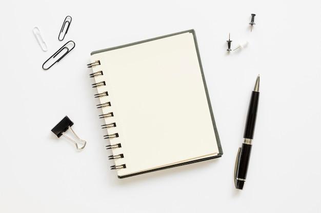 Bovenaanzicht van kantoorbenodigdheden met notebook en papier pinnen